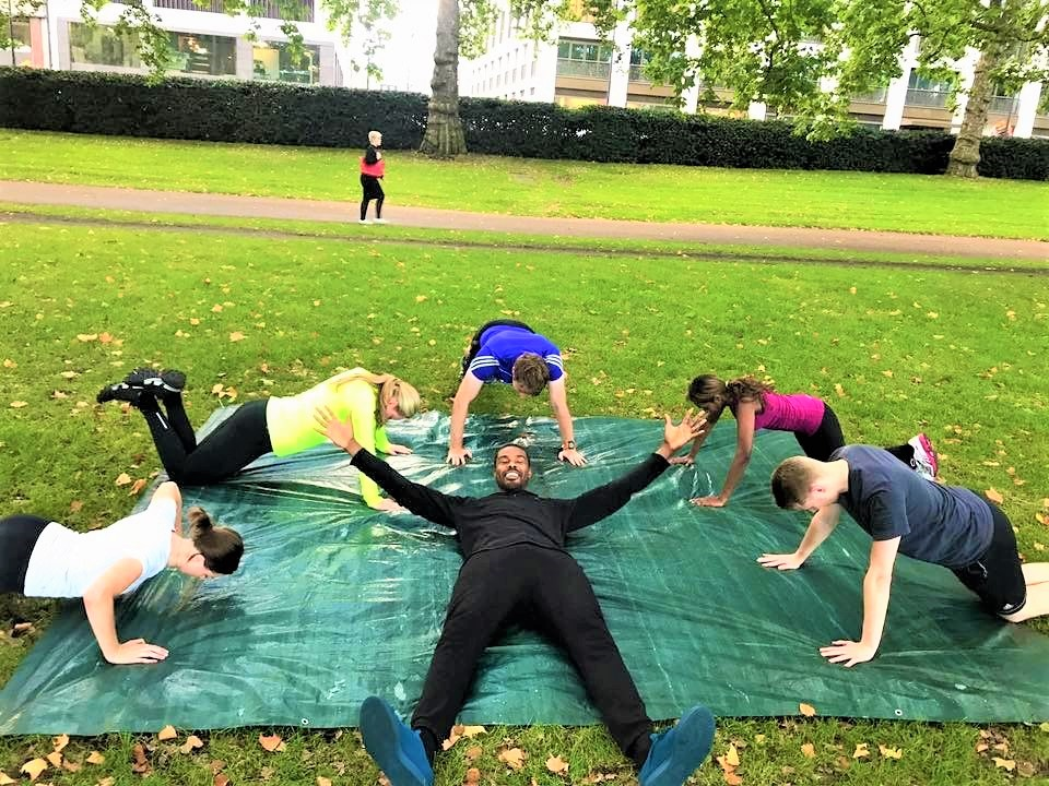 Martyn Barnard with GB Active Bootcamp members in green park London doing press ups